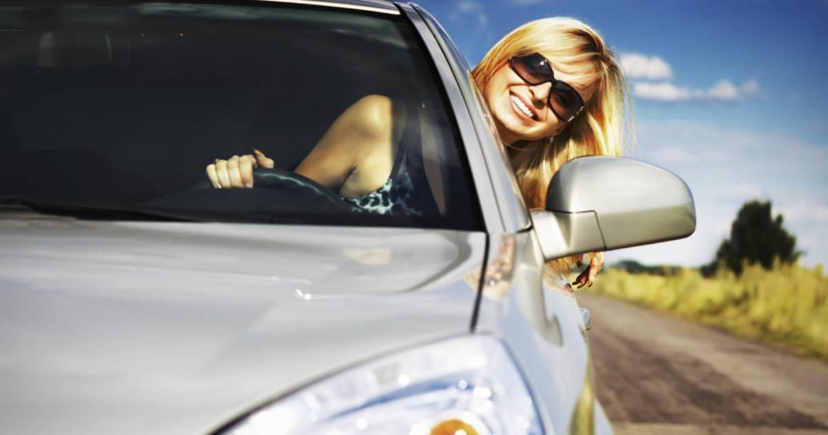 blonde vrouw met zonnebril rijd met hoofd buiten het raam