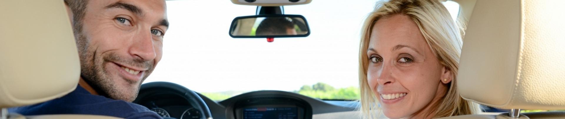 Man en vrouw zitten in de auto en kijken naar achteren